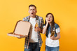 Young shocked couple woman man sport fans cheer up support team holding beer bottles italian pizza in cardboard flatbox clinging to head isolated on yellow background. Sport family leisure lifestyle.