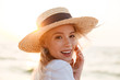 Leinwanddruck Bild - Cute blonde woman wearing hat outdoors at the beach