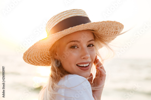 Leinwanddruck Bild Cute blonde woman wearing hat outdoors at the beach