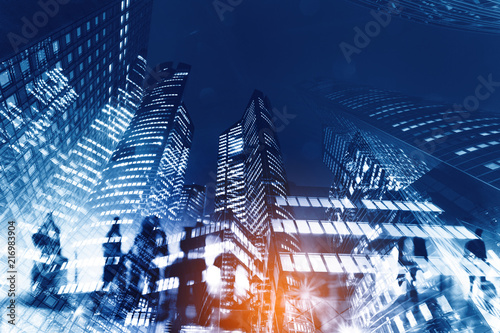Silhouettes of people walking in the street near skyscrapers and modern office buildings in Paris business district. Multiple exposure blurred image. Economy, finances, business concept illustration - 216983904