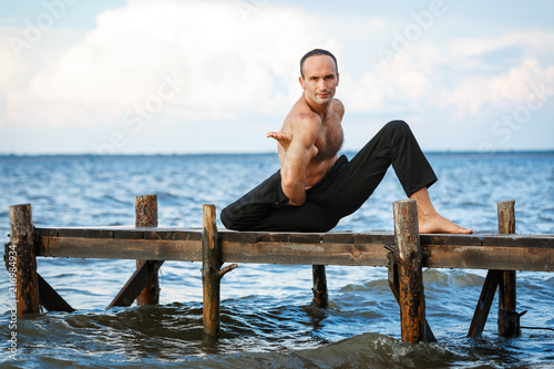 Wall mural Young yoga trainer practicing yoga exercises on a wooden pier on a sea or river shore