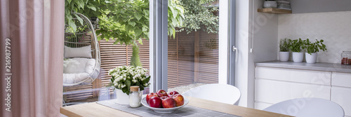 Leinwanddruck Bild Real photo of fresh apples on plate placed on wooden dining table standing in bright kitchen interior with glass door to terrace and countertop with plants