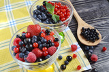 berries are red and blue in a glass bowl on a black wooden background