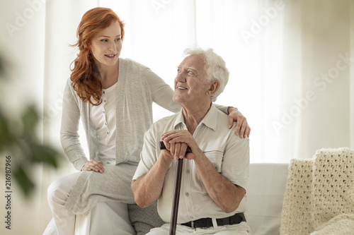 Smiling senior man with walking stick and his happy daughter at home - 216987966