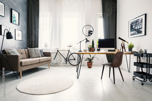 Modern home office interior with a big window, sofa, bike and desk with a computer. Place your product - 216988148