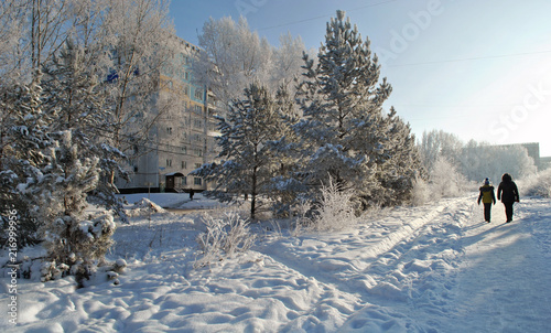 Foto Murales The street of the town in winter, snowy trees, a woman and a child are walking along the snowy path.