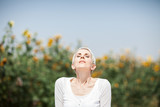 Beautiful middle age woman in a rural field scene outdoors with sunflowers, enjoying sunlight, summerly, autumn mood  - 217002546