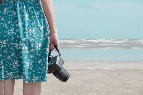Kobieta w błękit sukni mienia profesjonalisty dslr kamera na plaży