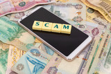 The word scam over a phone on top of a pile of dirham banknotes. Concept for money scam over the phone.