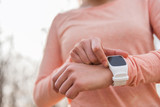 Wearable sport watch technology device for running. Active runner woman getting ready setting smartwatch app.