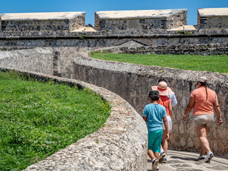 Tourists visiting a Spanish-colonial style fortified structure in Mexico