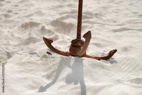 In de dag Zanzibar Rusty anchor on white sand on the beach in hot weather