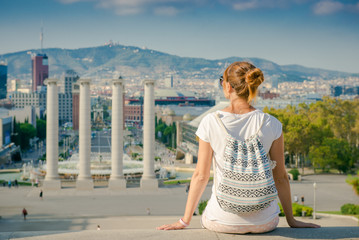 Girl tourist with a backpack looking at Barcelona. Girl sitting back and admiring the view of the city. Spain, walk around the city