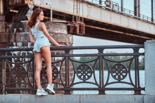 Back view of a sensual girl dressed in shorts and t-shirt leaning on the guardrail at the embankment against a bridge.
