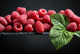 Ripe raspberries with green leaves on a black background.