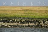 Fahrrinne zum Sielhafen an der Nordsee und Windräder mit Grasland - Stockfoto
