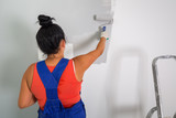Woman at painting a room with paint roller - 217041702