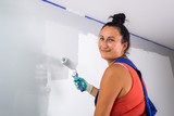 Woman at painting a room with paint roller - 217041725