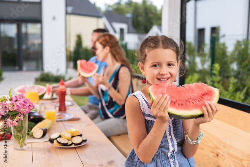 Foto Murales Sweet watermelon. Cute small girl smiling while enjoying her watermelon