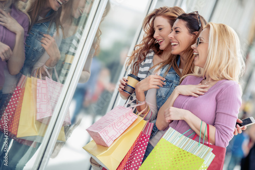 Happy surprised young women with shopping bags in the city - 217049350
