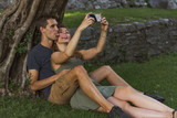 Young Couple in Love sitting under a tree in a castle - 217051597