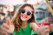 Quadro Joyful smiling girl in pink sunglasses making selfie in front of carousel. Outdoor portrait of cute stylish woman having fun in amusement park.