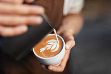 Coffee Art In Cup. Closeup Of Hands Making Latte Art