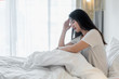 Attractive young Asian woman wake up on her bed looking unhappy and feeling sick..