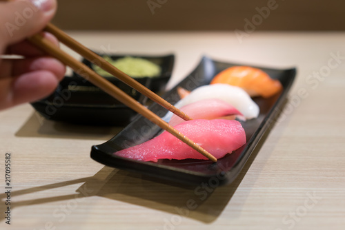 Foto Spatwand Sushi bar Chopsticks with Japan raw tuna sushi and fresh mix sushi set in black plate - Japanese food set style at Japanese restaurant..