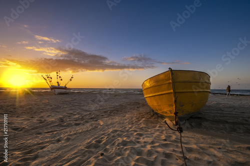 Foto Spatwand Strand sunset on the sea beach, boats on the sand