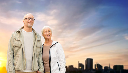 old age, tourism, travel and people concept - happy senior couple holding hands over tallinn city and evening sky background