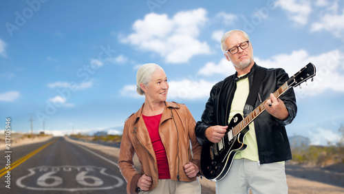 Foto Spatwand Route 66 rock music, old age and travel concept - happy senior couple with electric guitar over us route 66 background