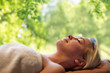 Quadro beauty, wellness and relaxation concept - beautiful young woman lying on massage table in spa over green natural background