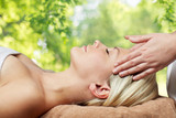 beauty, wellness and relaxation concept - close up of beautiful young woman lying with closed eyes and having face or head massage in spa over green natural background