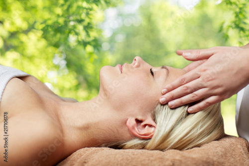 Foto Murales beauty, wellness and relaxation concept - close up of beautiful young woman lying with closed eyes and having face or head massage in spa over green natural background