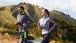 fitness, sport, people and healthy lifestyle concept - happy couple running over big sur hills and road background in california