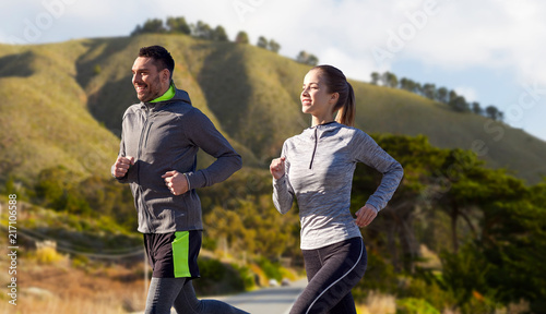 Foto Spatwand Hardlopen fitness, sport, people and healthy lifestyle concept - happy couple running over big sur hills and road background in california