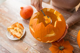 halloween, decoration and holidays concept - close up of woman with spoon carving pumpkin flesh and making or jack-o-lantern at home - 217108929