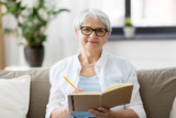 age, leisure and people concept - happy senior woman in glasses writing to notebook or diary at home - 217109984