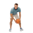 sport, leisure and people concept - smiling young man playing basketball over white background
