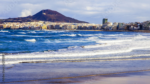 Fotobehang Canarische Eilanden Las-Palmas de Gran Canaria, Spain, on January 10, 2018. The winter sun lights the Playa de Las Canteras beach on the bank of the Atlantic Ocean. beautiful embankment in the distance