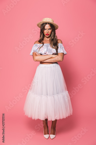 Leinwanddruck Bild Full length portrait of upset offended woman 20s wearing straw hat and fluffy skirt pouting in resentment with arms crossed, isolated over pink background