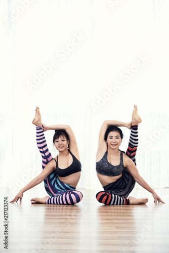 Wall mural Stretching women at yoga class