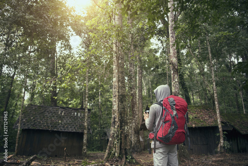 Foto Murales Freedom traveler man standing with backpack and enjoying a beautiful nature forest.