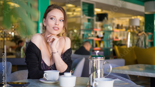 Foto Murales Young Woman Drinking Tea in a Cafe Outdoors. Summer City Background. Toned Photo