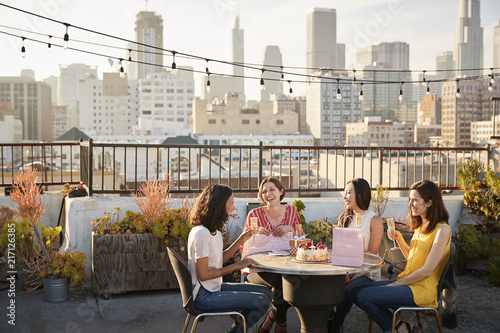Foto Murales Female Friends Celebrating Birthday On Rooftop Terrace With City Skyline In Background