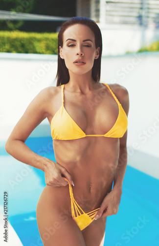 Sexy woman in yellow bikini posing at swimming pool | Buy Photos ...