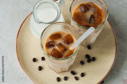 Wall mural Iced coffee in a tall glass served on a plate on a white background. Overhead view.