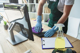 cropped shot of professional cleaner in rubber gloves cleaning computer keyboard in office - 217135316