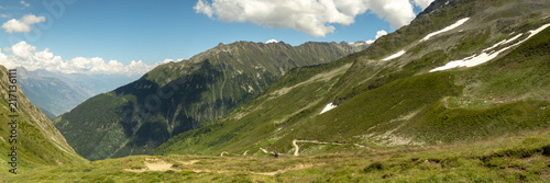 view of mont blanc and the valley surrounding chamonix in the french alps during summer showing green alpine meadows, pristine mountains and clear blue skies